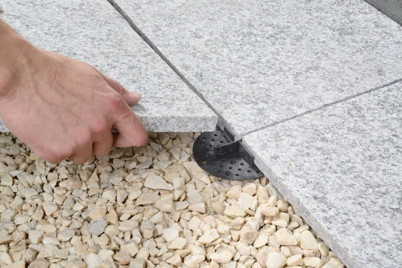 Paving tiles on sand laying with porcelain cross spacers