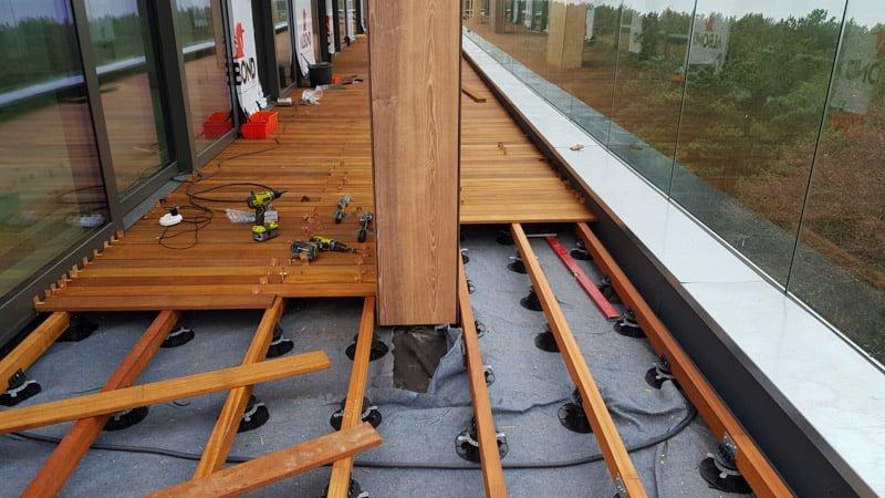 Beispiel für die Montage einer typischen erhöhten belüfteten Terrasse an, auf der verstellbaren Stelzlager die unter Balken verlegen sind.