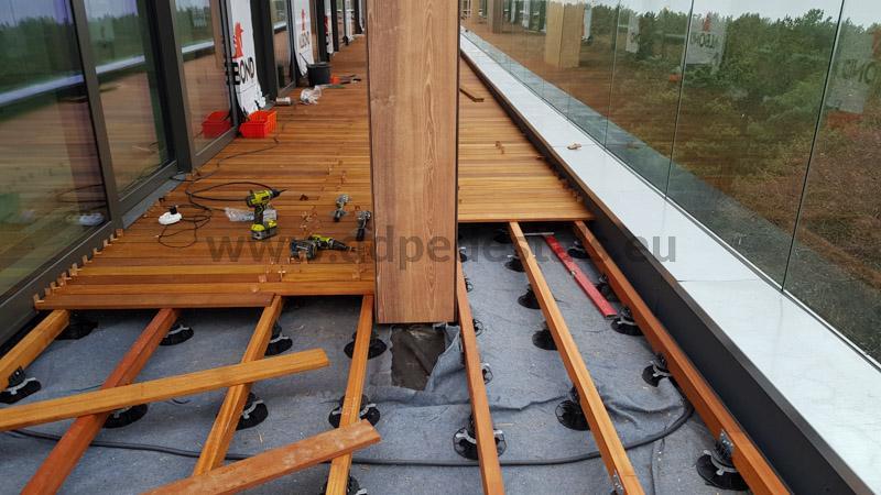 Sehen Sie sich ein Beispiel für die Montage einer typischen erhöhten belüfteten Terrasse an, auf der verstellbaren Stelzlager die unter Balken verlegen sind.