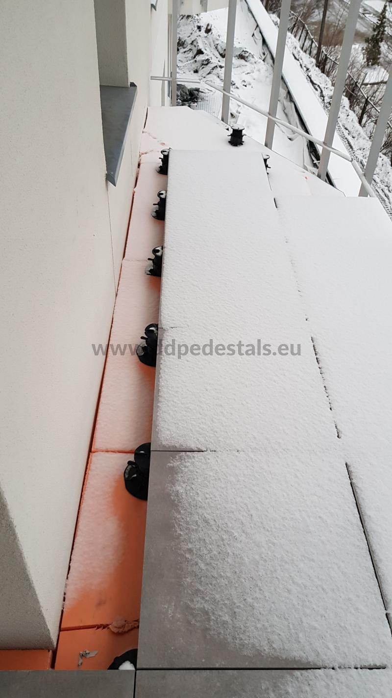laying terrace tiles on brackets in winter during frost and snow