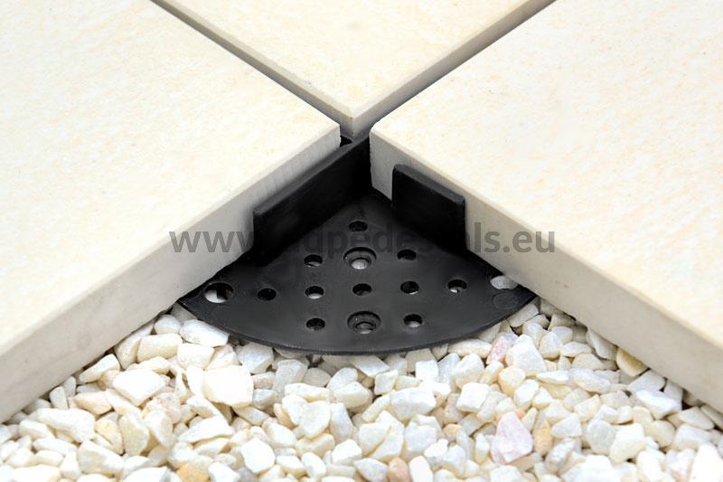 Schwarzes Plattenlager unter Terrassenplatten zur Trockenmontage, z. B. auf Kies.