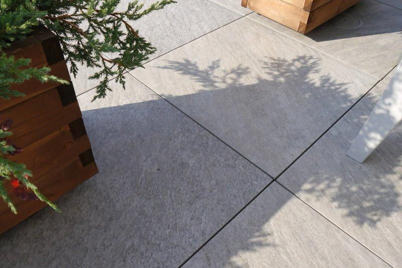 Une terrasse en carreaux de céramique peut supporter le poids d'un grand pot en bois