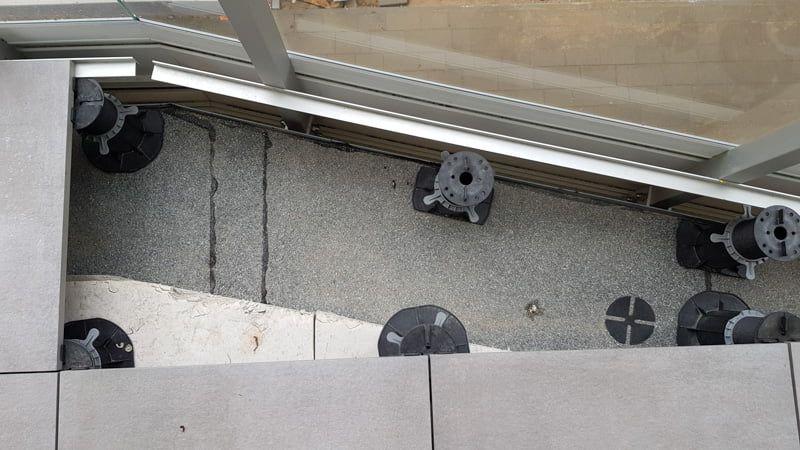 Ein Winkel, der an die Balustradenpfosten geschraubt ist, um die Terrassenfliesen zu stützen