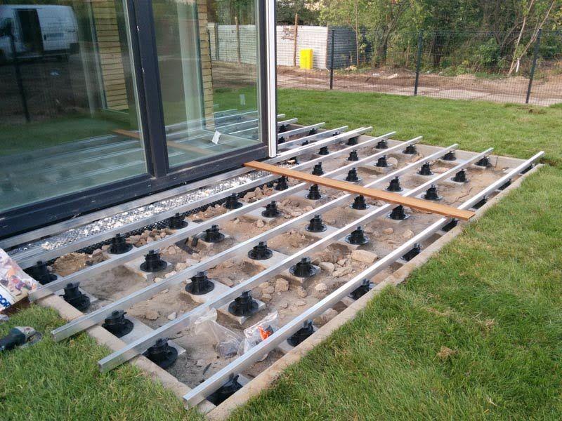 Aluminiumbalken auf der Unterkonstruktion der Terrasse auf dem Boden