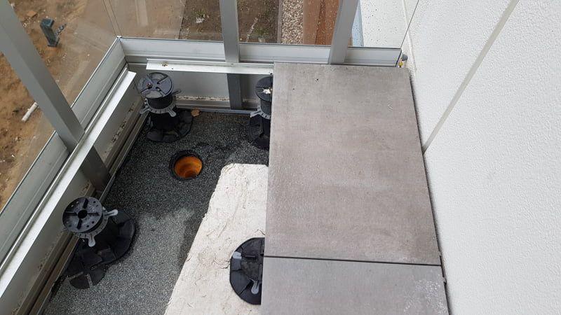 un angle vissé aux poteaux de balustrade pour supporter les dalles de terrasse