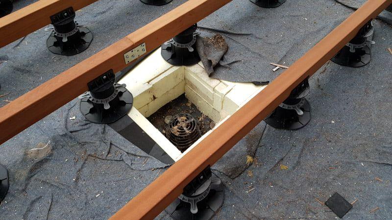 Maskierung der Entwässerung unter der Terrasse mit Brettern auf Stelzlager