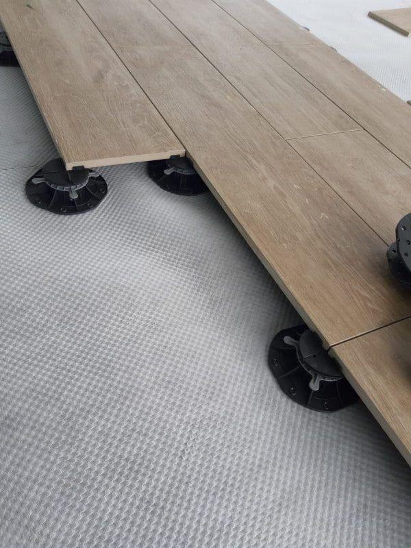 panneaux en céramique imitation bois reposant sur des plots réglables